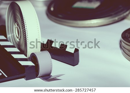 Two rolls of film, boxes of film and cinema slapstick. toned image - stock photo