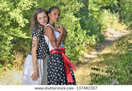 Two romantic girl surrounded by leaves in forest - stock photo