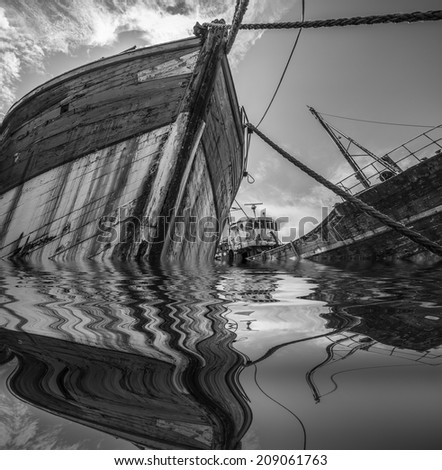 two romantic old fishing boats - wrecks - black and white picture - stock photo