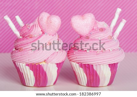 Two romantic pink cupcakes with heart and straws - stock photo
