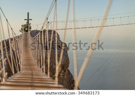 Two rope ladders  over abyss leading to catholic cross standing on top of mountain - stock photo