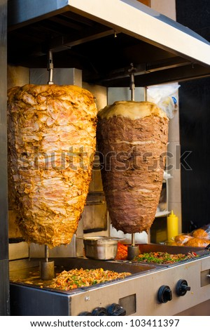 Two rotating skewered chicken and lamb meat grilled in stainless steel grill and ready to serve in a typical Middle Eastern fast food kebab sandwich - stock photo