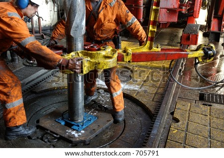 Two roughnecks breaking a connection with help from tongs. Offshore oil rig. - stock photo