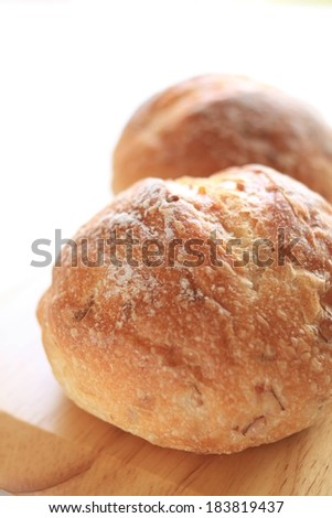 Two round loaves of bread sitting on a board. - stock photo