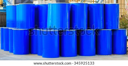Two rows of big blue barrels standing on asphalt - stock photo