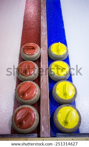 Two rows of red and yellow curling rocks lined up  - stock photo