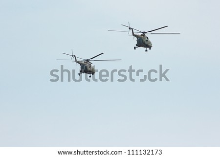 Two russian military transport helicopter MI-8 in the cloudy sky - stock photo