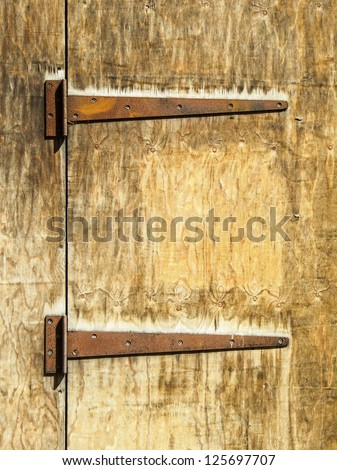 Two rusty hinges on an old wooden door - stock photo