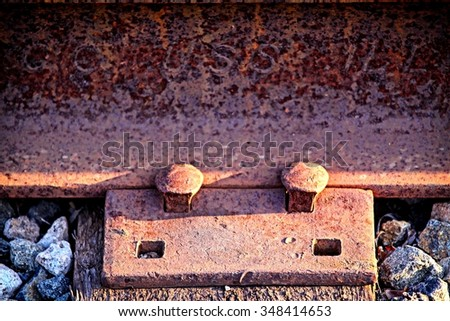 Two rusty old nails fastening a train track. - stock photo