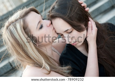 Two sad girls sorry for each other outdoors - stock photo