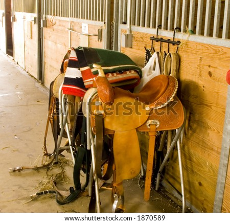 Two saddles and tack in barn. - stock photo
