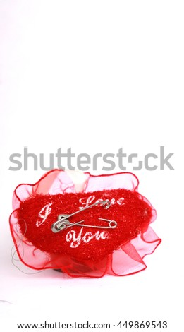Two Safety pins on a red pincushion with text i love you.love concept  - stock photo
