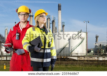 Two safety specialists monitoring the perimeter of a petrochemical refinary, using electroncial devices, such as cb radios and tablets - stock photo