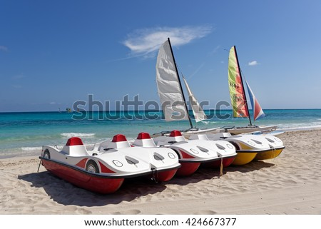 Two sail boats and three pedal boats on a tropical beach with blue sky and water background - stock photo