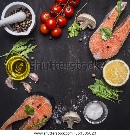 Two salmon steak, butter, salt and pepper, lemon and cherry tomatoes, garlic, herbs place for text,frame on wooden rustic background top view - stock photo