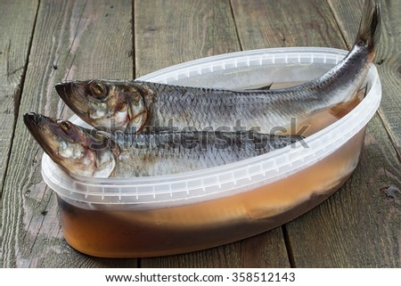 Two salted herrings in plastic container with brine and spices on a wooden table - stock photo