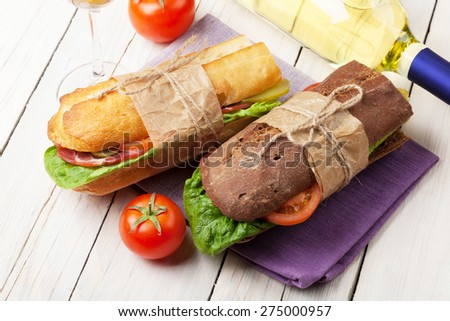 Two sandwiches and white wine on wooden table  - stock photo