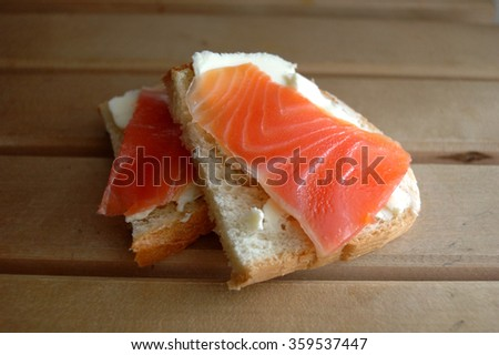 Two sandwiches with red fish and butter. - stock photo