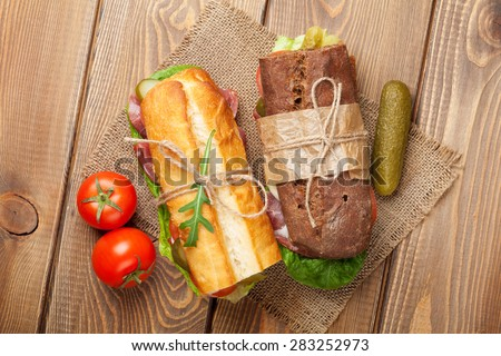 Two sandwiches with salad, ham, cheese and tomatoes on wooden table. Top view - stock photo