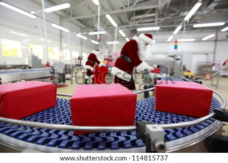 Two Santa Clauses working in Xmas Gifts Factory - stock photo
