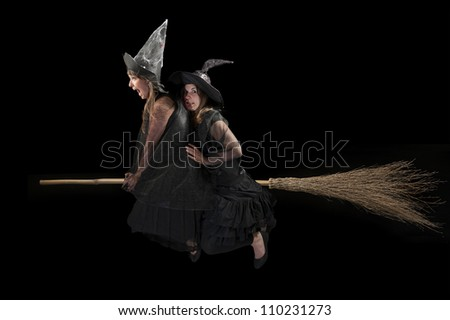 two scared witches flying on a broom - stock photo