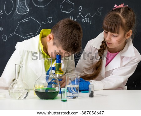 two schoolchildren in white gowns watching chemical experiment in lab - stock photo
