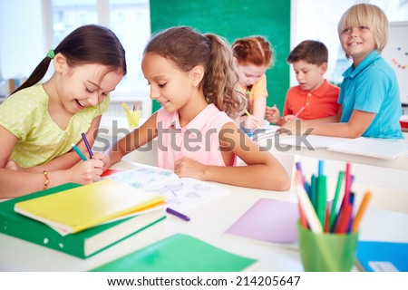 Two schoolgirls drawing in group on background of classmates - stock photo