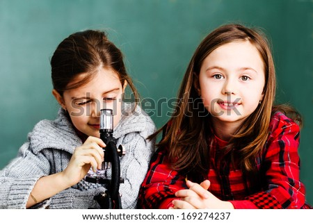 Two schoolgirls have a practice with microscope - stock photo