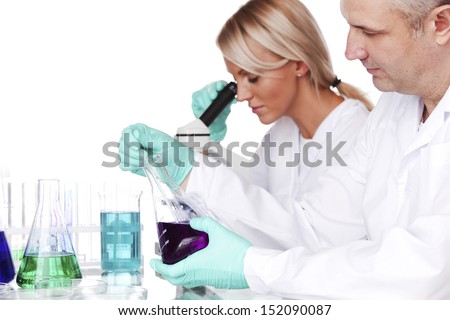 two scientist in chemical lab conducting experiments - stock photo
