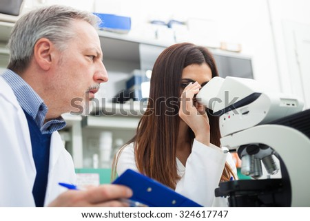 Two scientists discussing a medical document in their laboratory - stock photo