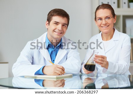 Two scientists looking at camera while working with chemical liquids in laboratory - stock photo