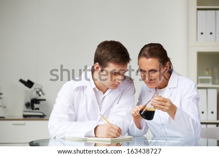 Two scientists looking at glass flask with liquid oil in laboratory while analyzing its characteristics - stock photo