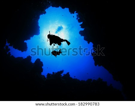 Two Scuba Divers descending into underwater cave - stock photo