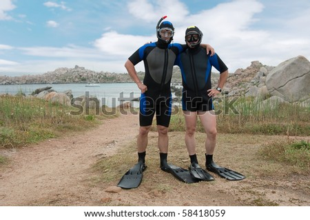 two scuba divers on island - stock photo