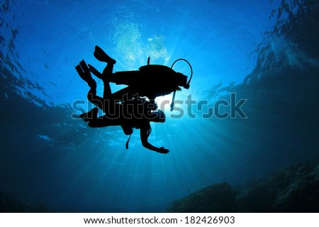 Two Scuba Divers silhouetted against sun - stock photo