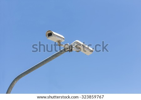 Two security camera on blue sky background - stock photo