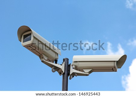 Two security cameras against blue sky - stock photo