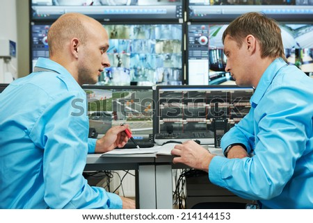 two security guards watching video monitoring surveillance security system - stock photo
