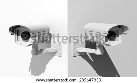 Two security surveillance cameras on white wall corner - stock photo