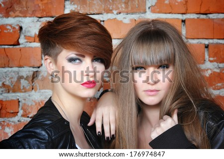 Two seductive young girls at the brick wall. Fashion portrait - stock photo