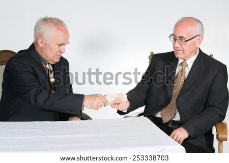 two senior businessmen, holding cash money (euro banknotes) - stock photo