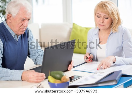 Two senior busy people checking the business plan - stock photo