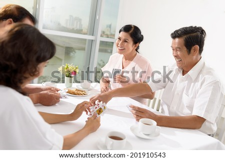 Two senior couple playing a game of cards - stock photo