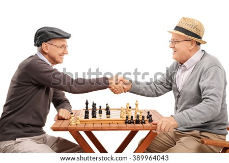 Two senior gentlemen shaking hands after playing a game of chess isolated on white background - stock photo