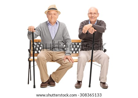 Two senior gentlemen with black canes sitting on a wooden bench and looking at the camera isolated on white background - stock photo