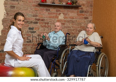 Two Senior In Wheelchairs During Physiotherapy, Looking At Camera - stock photo