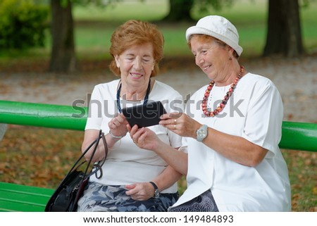Two senior ladies reading news on tablet in the park - stock photo