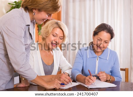 Two senior ladies signing documents at bank and smiling - stock photo