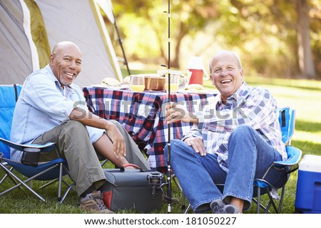 Two Senior Men On Camping Holiday With Fishing Rod - stock photo