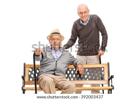 Two senior old friends posing together seated on a wooden bench isolated on white background - stock photo